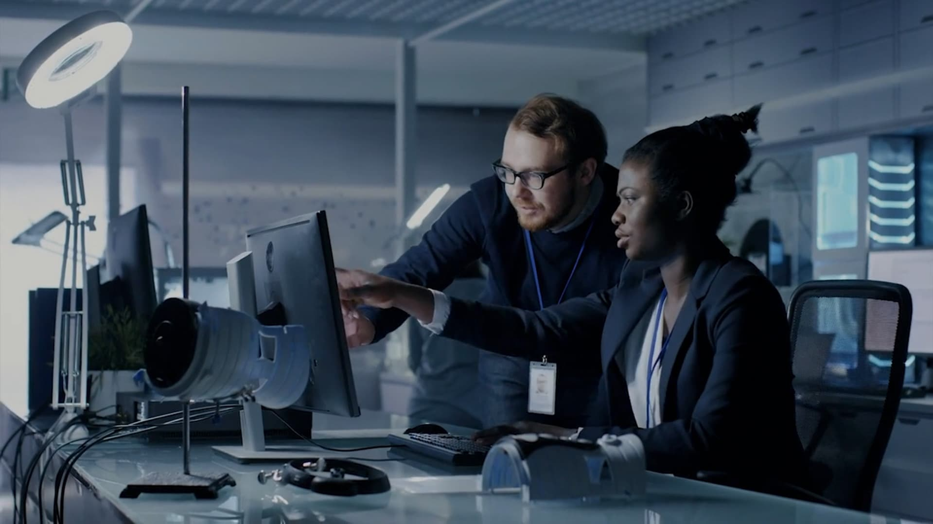 A man and woman discussing work in front of a computer screen